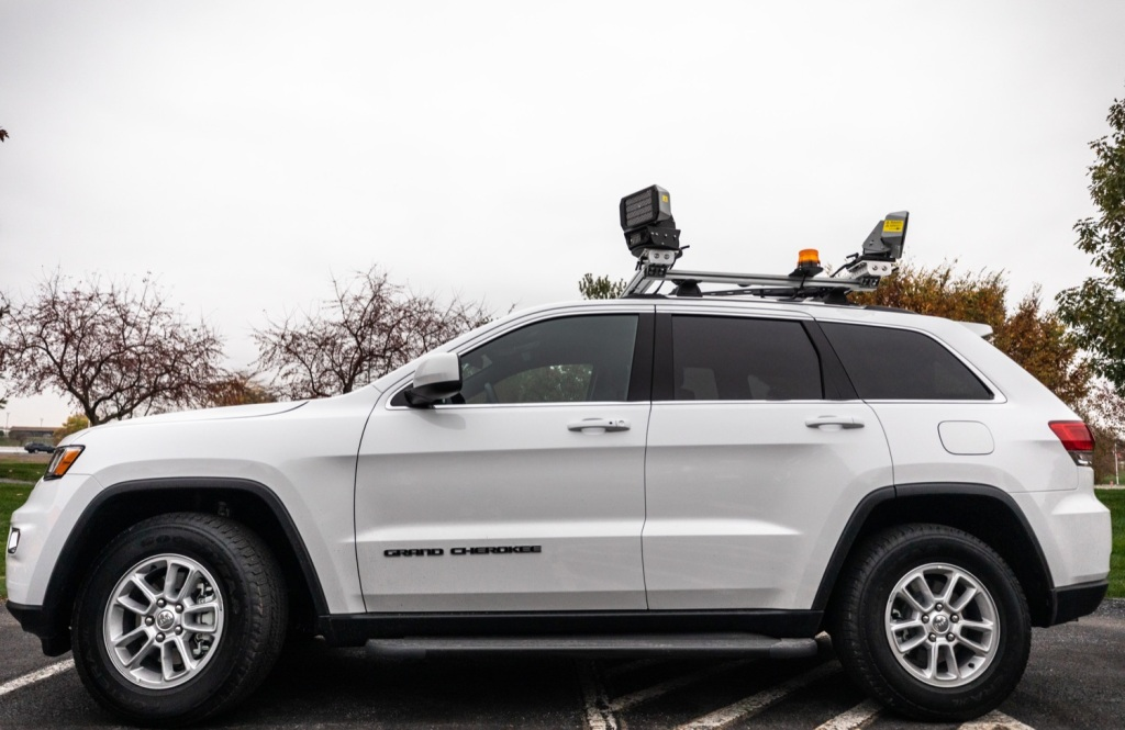 A speed camera system mounted to a white SUV
