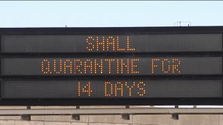 A highway sign urges quarantine for visitors to Maine