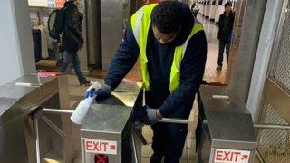 Man wipes down transit turnstiles