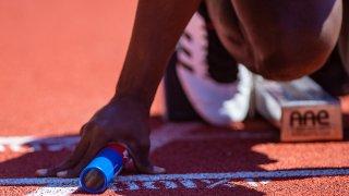 Relay runner holds baton on track