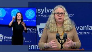 A woman at a podium with a sign language interpreter