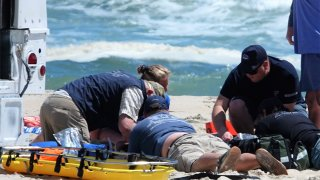 Rescuers work on person on beach