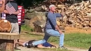 A man kneels on another man's back with flags near him