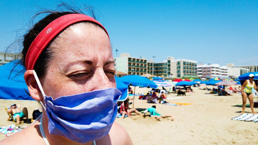Woman on the beach wearing a mask