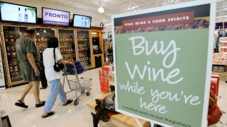 In this June 25, 2010 photo, shoppers walk past the wine selection offerings from the Pennsylvania Liquor Control Board's self-serve wine kiosk at a Giant food store in Harrisburg, Pa.