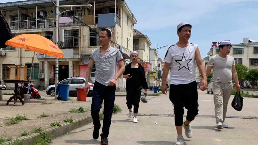 In this June 5, 2019, photo, residents of the Hui Muslim ethnic minority walk in a neighborhood near an OFILM factory in Nanchang in eastern China's Jiangxi province. The Associated Press has found that OFILM, a supplier of major multinational companies, employs Uighurs, an ethnic Turkic minority, under highly restrictive conditions, including not letting them leave the factory compound without a chaperone, worship, or wear headscarves.