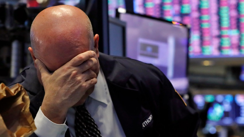 A trader has his head in his hand on the floor of the New York Stock Exchange, Thursday, March 12, 2020.
