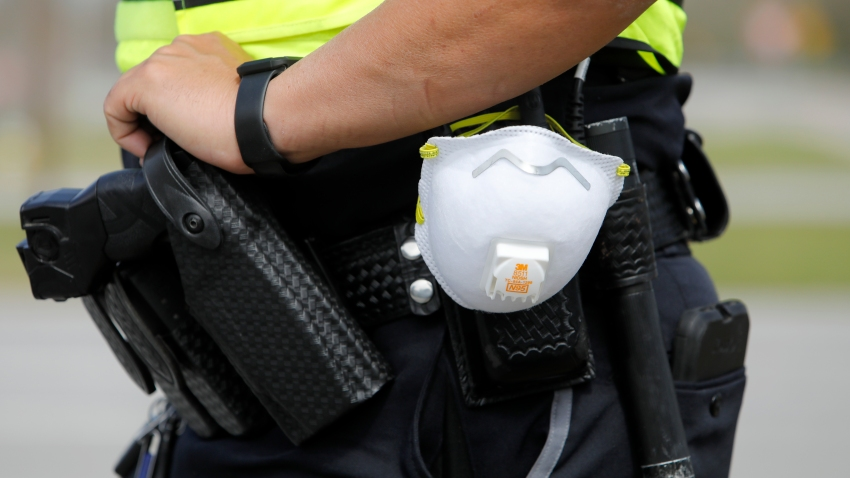 a North Charleston police officer carries a protective mask around his gun belt