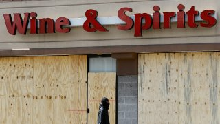 A pedestrian walks past a boarded up Wine and Spirits store, March 18, 2020, in Upper Darby, Pennsylvania. The state has shut down all of its roughly 600 state-owned wine and liquor stores to try to slow the spread of the new coronavirus.