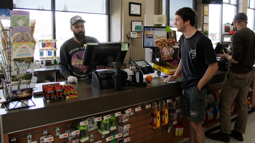 Mike Johnston, a clerk at the Maupin Market in tiny Maupin, Oregon, helps a customer while wearing latex gloves