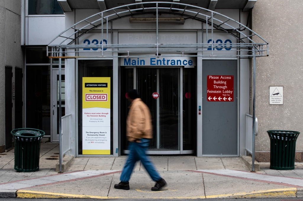 A pedestrian walks past the shuttered Hahnemann Hospital in Philadelphia, Wednesday, March 25, 2020.