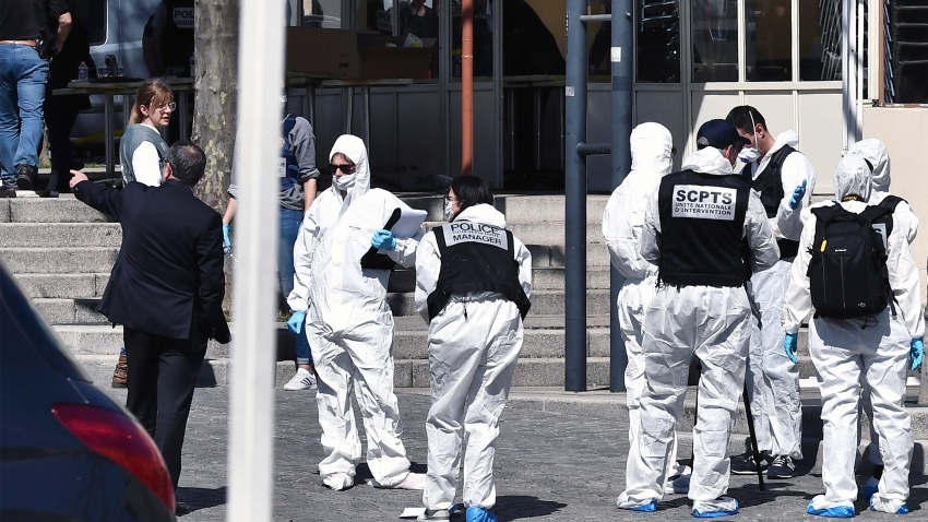Police officers investigate after a man wielding a knife attacked residents venturing out to shop in the town under lockdown, Saturday April 4, 2020 in Romans-sur-Isere, southern France.