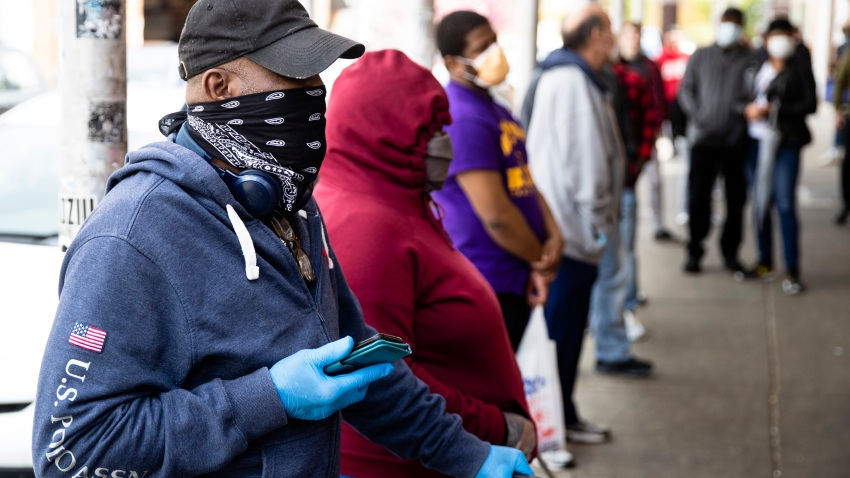George Ricketts, wearing a face covering to protect against the spread of the new coronavirus, waits to enter a store