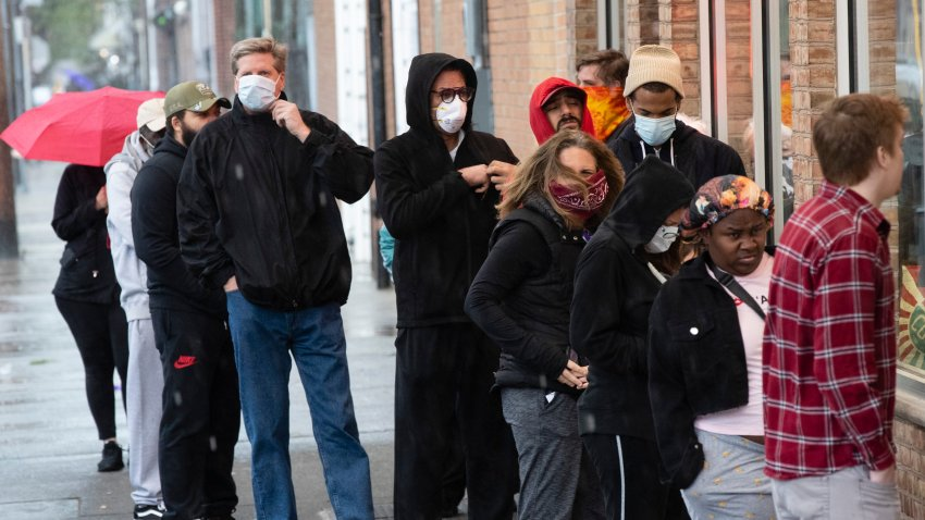 Shoppers wearing masks and face coverings wait in line to enter a store on South 9th Street in Italian Market neighborhood of Philadelphia, Thursday, April 9, 2020.
