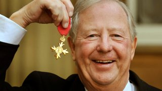 Tim Brooke-Taylor holds his OBE after being presented it by Queen Elizabeth, outside Buckingham Palace in London.