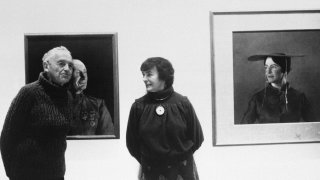 """American artist Andrew Wyeth poses with his wife Betsy in front of his paintings """"The Patriot,"""" left, and """"Maga's Daughter"""" for which Betsy was the model, in this 1985 photo. Betsy James Wyeth, the widow, business manager and muse of painter Andrew Wyeth, died Tuesday, April 21, 2020, at age 98, according to the Brandywine River Museum of Art in Chadds Ford, Pa., which she helped found."""