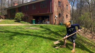 Wyatt Anthony, 13, covers an apple core with dirt as part of his effort to grow an apple tree at the side of his front yard in Allison Park, Pennsylvania, April 21, 2020. Wyatt has not been within 50 feet of an acquaintance outside his immediate family since March 13.