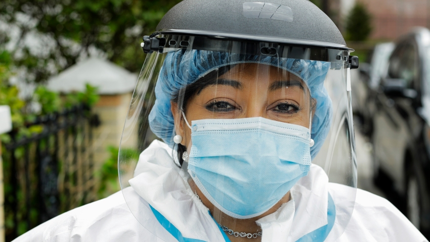 In this Thursday, April 30, 2020, photo, Linda Silva, a nurse's assistant, poses for a portrait in the Queens borough of New York. Silva, who tested positive for COVID-19, returned to work after recovering. It's been more than a month since she has hugged her two sons or her husband.