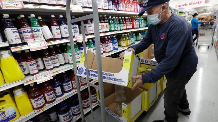 In this Wednesday, June 3, 2020 photo, Juan Santos stocks shelves at the Presidente Supermarket in the Little Havana neighborhood of Miami.