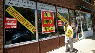 In this June 23, 2020, file photo, a man walks past a retail store that is going out of business due to the coronavirus pandemic in Winnetka, Ill.
