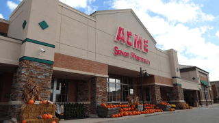 """A storefront reads """"ACME Savon Pharmacy."""" At the entrance sit various pumpkins."""