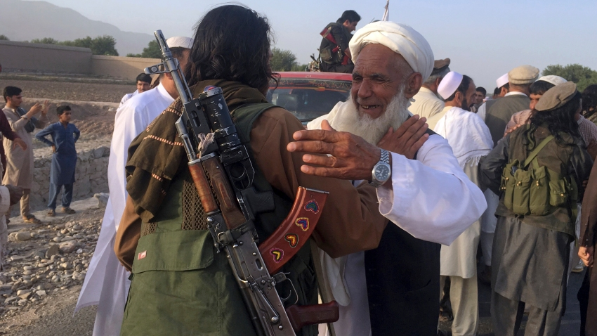 In this June 16, 2018 file photo, Taliban fighters gather with residents to celebrate a three-day cease fire marking the Islamic holiday of Eid al-Fitr, in Nangarhar province, east of Kabul, Afghanistan. Many Afghans view Saturday's expected signing of a U.S.-Taliban peace deal with a heavy dose of well-earned skepticism. They've spent decades living in a country at war -- some their whole lives — and wonder if they can ever reach a state of peace.