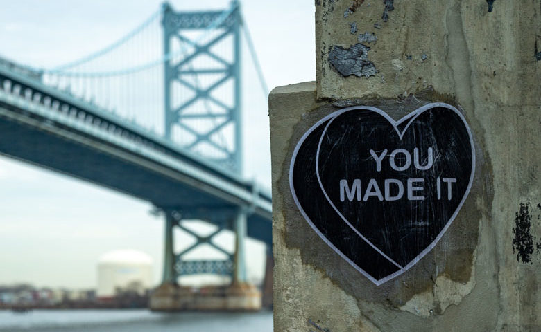 """You made it"" heart on cement pillar with Ben Franklin Bridge in background."