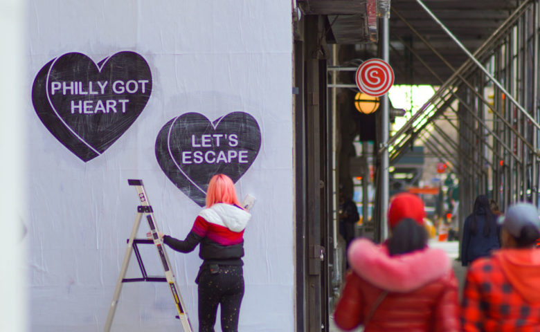 Woman artist with ladder putting up black and white heart art on white wall