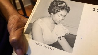 """In this March 4, 2020 photo, Roslyn Pope shows her Spelman College yearbook at her home in Atlanta. As a 21-year-old Spelman senior in March 1960, Pope wrote """"An Appeal for Human Rights,"""" a document that made the case for the Atlanta Student Movement, a nonviolent campaign of boycotts and sit-ins by black college students that protested racial segregation in education, jobs, housing, voting, hospitals, movies, concerts, restaurants and law enforcement."""