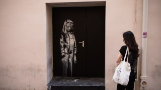 In this June 26, 2018, file photo, Banksy's art is seen on a side street next to the Bataclan concert hall where a terrorist attack killed 90 people in 2015, in Paris, France.