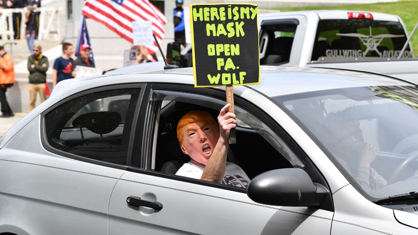 "A car passenger disguised behind a Trump mask wields a sign as part of a ""reopen"" Pennsylvania demonstration on April 20, 2020, in Harrisburg, Pennsylvania."