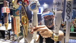 In this July 1, 2020, file photo, a bartender pours a beer while wearing a mask and face shield amid the coronavirus pandemic at Slater's 50/50 in Santa Clarita, Calif.