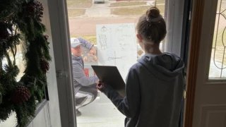 Girl receives math tutoring through her window as teacher helps from outside