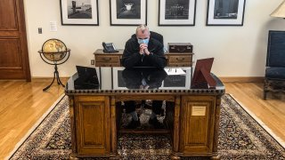New Jersey Governor Phil Murphy observes a moment of silence for George Floyd, a Black Minneapolis man who died during an arrest by police, on a desk inscribed with Woodrow Wilson's name, June 4, 2020. Murphy said he has since found a replacement for the desk after people pointed out that Wilson defended slavery and practiced segregation.