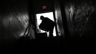 A volunteer is seen in silhouette as he carries cartons of food donations at St. Stephen Outreach in the Brooklyn borough of New York, March 20, 2020.