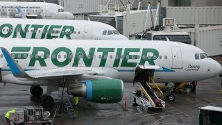 Frontier Airlines Inc. planes sit on the tarmac at Denver International Airport