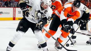 Sidney Crosby #87 of the Pittsburgh Penguins tries to control the puck as James van Riemsdyk #21 of the Philadelphia Flyers tries to get it
