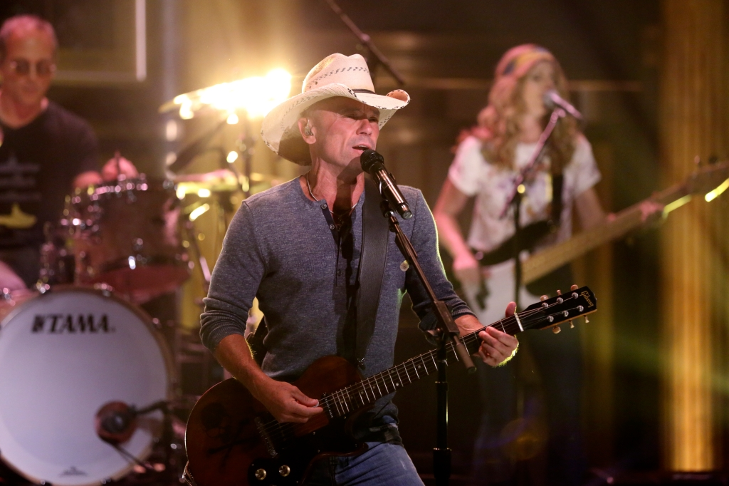 Kenny Chesney Performing on The Tonight Show with a guitar in his hand. A guitarist and drummer are  behind him.