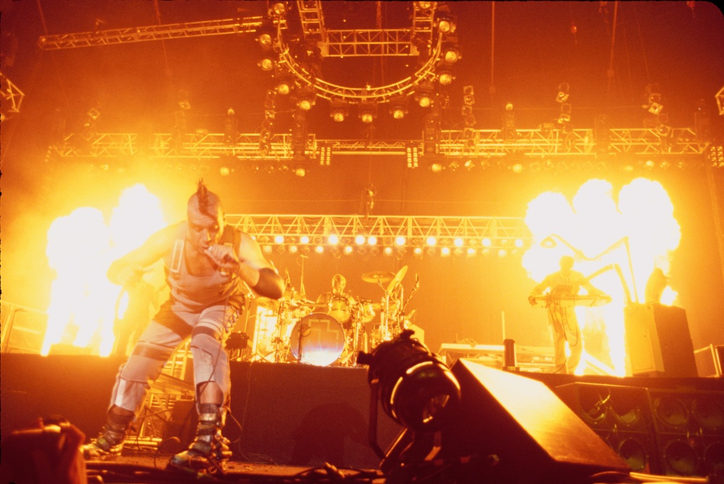 Fire shoots from the floor as Rammstein performs on stage.