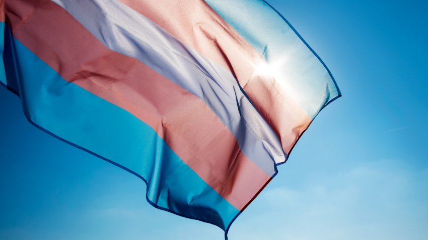 closeup of a transgender pride flag waving on the blue sky, moved by the wind, with the sun in the background