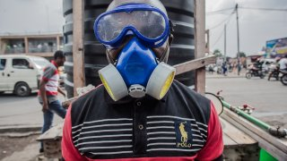 In this file image, a health worker looks on as he wears protective gear to mix water and chlorine in Goma on July 31, 2019.