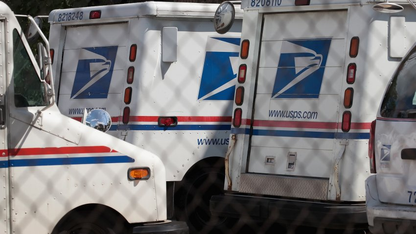 United States Postal Service (USPS) trucks are parked at a postal facility