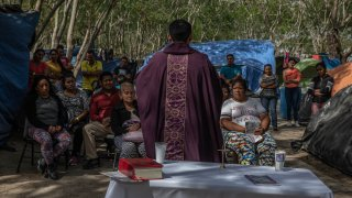 A priest holds a mass for asylum seekers at a makeshift migrant camp in Matamoros, Tamaulipas state, Mexico