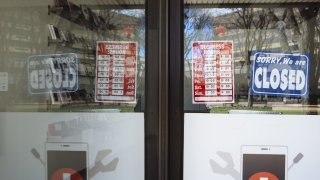 """a """"Closed"""" sign hangs in the window of a phone repair shop"""
