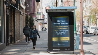 A person wearing a protective mask passes a sign about the stay at home order in downtown Philadelphia, Pennsylvania