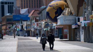 A couple walks on the boardwalk past shuttered stores during the coronavirus pandemic on May 7, 2020 in Atlantic City, New Jersey.