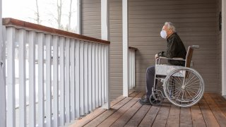 Senior man in wheelchair wearing protective mask to prevent coronavirus transmission on porch