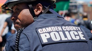 Police officers of the Camden County Police Department keep an eye out as demonstrators take part in a Black Lives Matter protest march in Camden, NJ on June 13, 2020. \