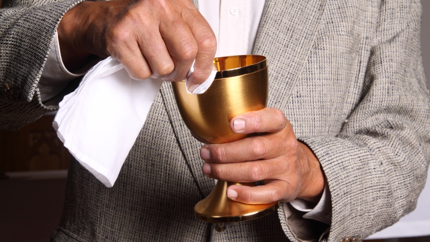 File photo of a man wiping the chalice during communion.