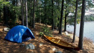 Canoeists camp with tent and canoe by the lake